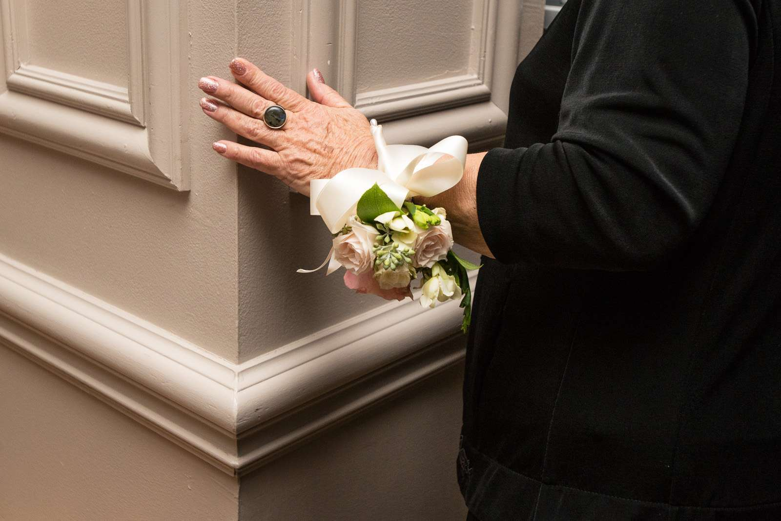 an older woman's hand with a corsage on a pillar