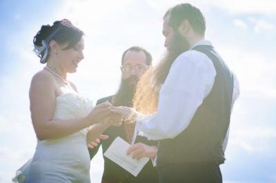 bride placing ring on grooms hand.jpg