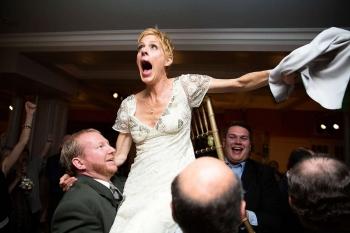 celebrating bride held aloft in chair.jpg